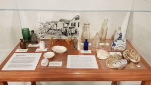 exhibit case containing bottles, shells, etc