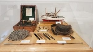 exhibit case containing rope, hat, model boat, fish hooks, sextant